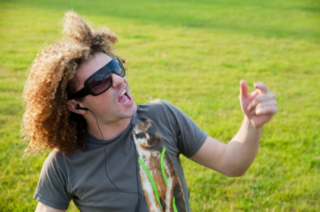 Portrait of an young guy listening to music on headphone and dancing in a park photo