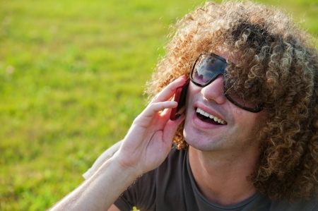 Young guy with curly hair sits on the grass and talk by phone photo