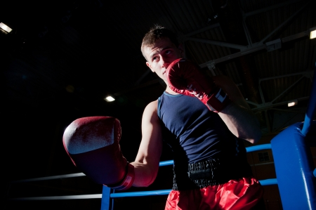 Young adult boxer fighting on the ring
