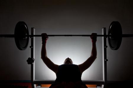 pesas: El hombre levantador de pesas en el gimnasio levantando pesas en un Benchpress