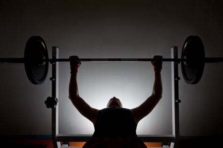 Man weightlifter at the gym, lifting weights on a benchpress photo