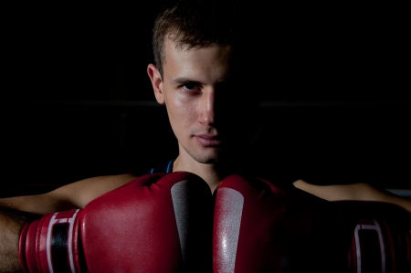 Portrait of young boxer with red gloves over black background