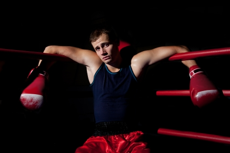 Young adult man sits in the corner of the ring