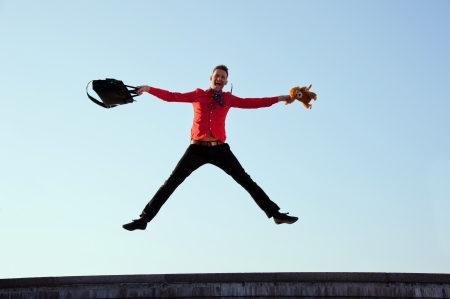 Happy businessman jumping near the stairs on the background of blue sky photo