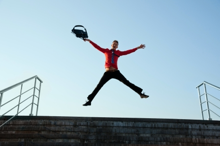 Happy businessman jumping near the stairs on the background of blue sky