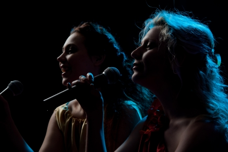 Two pretty women singing in microphone over the black background