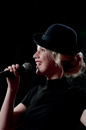 Pretty woman singing in microphone over the black background photo
