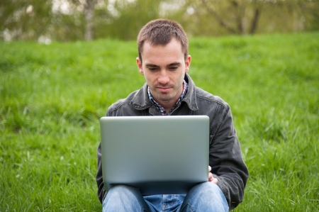Young man with notebook sitting in the park photo