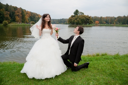 Handsome bride and funny groom stands in the park near the river photo