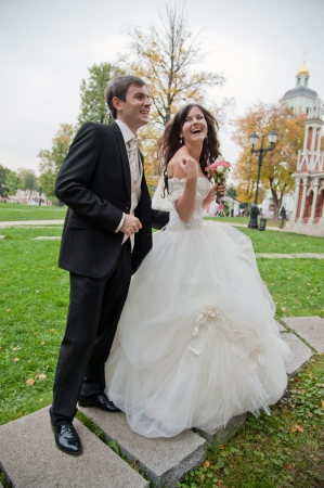 Handsome bride and funny groom stands in the park photo