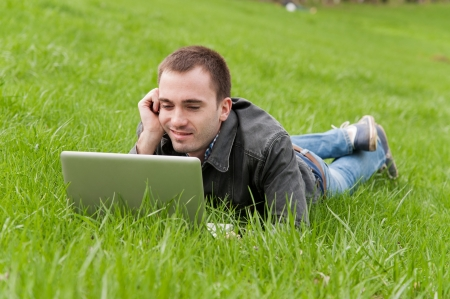 Young man with notebook lying in the park photo