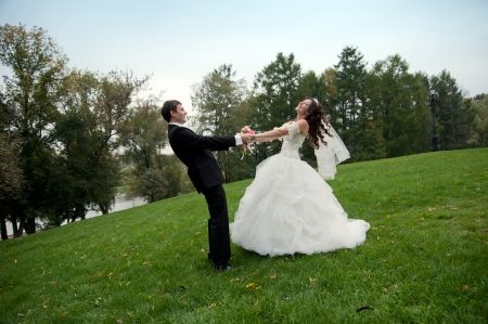 Newly married couple dancing in field. Outdoor portrait of bride and groom photo