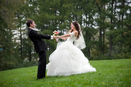 Newly married couple dancing in field. Outdoor portrait of bride and groom