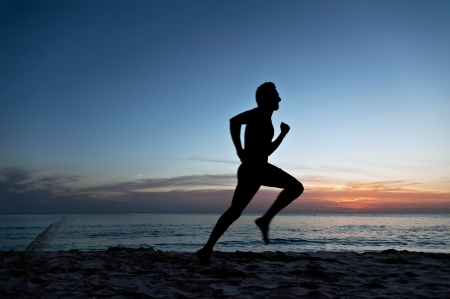 Young man running on the beach at the sunset