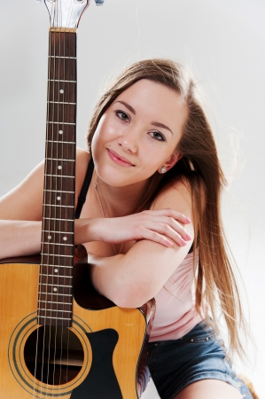 Portrait of beautiful smiling woman with guitar