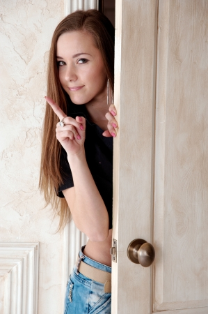 adult wall: Portrait of young beautiful smiling woman near the door