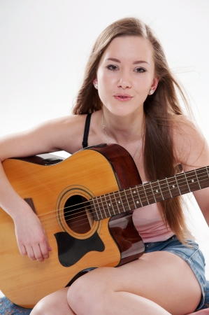 Portrait of beautiful smiling woman with guitar photo
