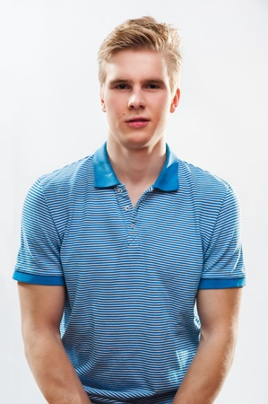 Portrait of young handsome blond man wearing shirt against grey background