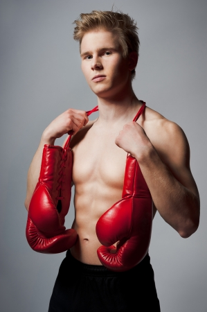 Portrait of a young blond man with boxing gloves against grey background photo