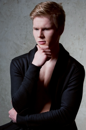 Portrait of young blond man thinking about something against grey background photo