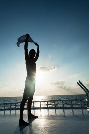 Man holding a shirt over his head against sea sunset, shot on the roof of the boat photo