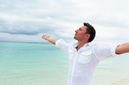 Man looking into the distance with his hands up against the sea and cloudy sky