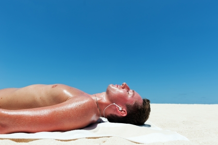 Man sunbathes and listens to music on the beautiful beach of white sand against the blue sky photo