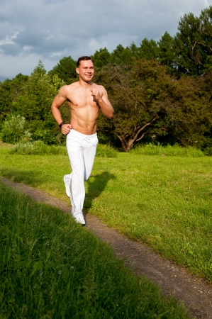 white pants: Man in white pants runs on the road in the park