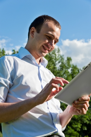Man stands with tablet in the park photo
