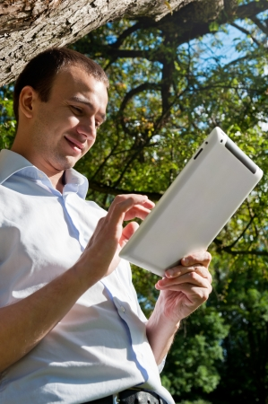 Man stands with tablet near the tree in the park photo