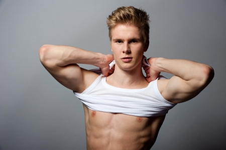 Portrait of young handsome blond man wearing t-shirt against grey background photo