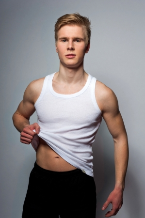 Portrait of young handsome blond man wearing t-shirt against grey background
