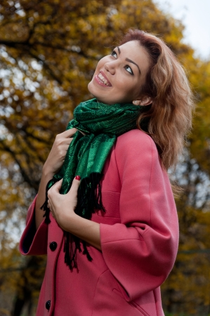 Beautiful woman in pink coat enjoy walking in autumn Park photo