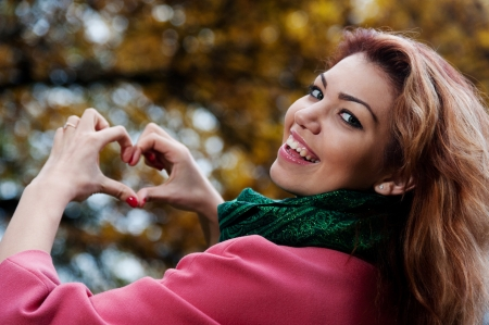 Beautiful woman in pink coat showing heart in the Park, autumn background photo