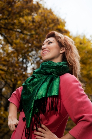 Beautiful woman in pink coat walks in the Park, autumn background photo