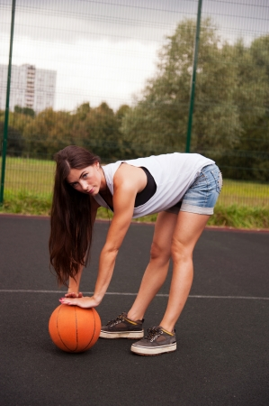 Sexy Woman Holding Basketball In Hand On Sports Playground photo