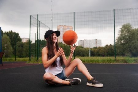Cute Girl Throw Basketball While Sitting On Sports Playground photo