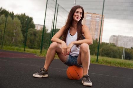 sitting ground: Sexy Woman Sitting On Basketball On Sports Playground Stock Photo
