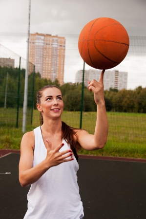 Sexy Woman Throw Basketball While Standing On Sport Playground photo