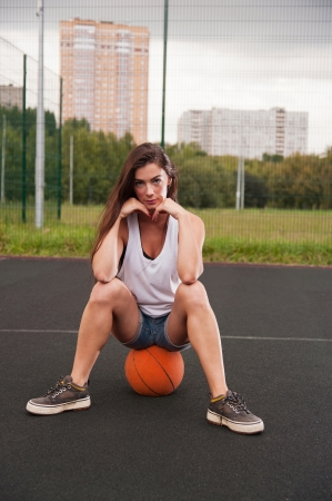 sitting on the ground: Woman Sitting On Basketball On Sports Playground