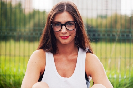 Portrait Of Young Woman Wearing Hipster Glasses On Sports Playground photo