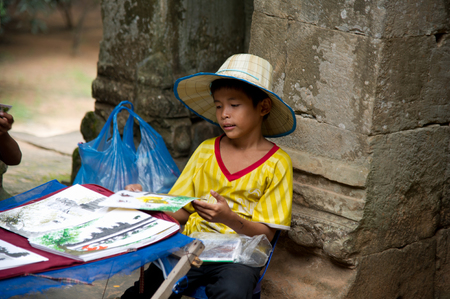 SIEM REAP, CAMBODIA - July 17, 2013: Little asian boy sitting with some souvenirs for sale in Angkor Wat temple, July 17, 2013, Siem Reap, Cambodia.