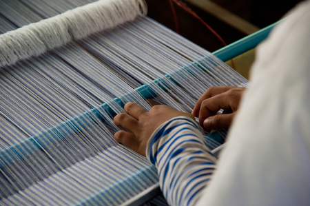 SIEM REAP, CAMBODIA - July 18, 2013: A weaver adjusts the silk cloth on her loom, July 18, 2013, near Siem Reap, Cambodia