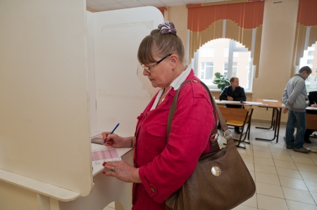 local election: MOSCOW, RUSSIA - SEPTEMBER 8, 2013  Woman fills election ballot with the candidates for mayor of Moscow on September 8, 2013 at the local election commission in Moscow