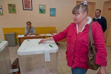 election commission: MOSCOW, RUSSIA - SEPTEMBER 8, 2013  Woman put election ballot with candidates for mayor of Moscow into the box on September 8, 2013 at the local election commission in Moscow  Editorial