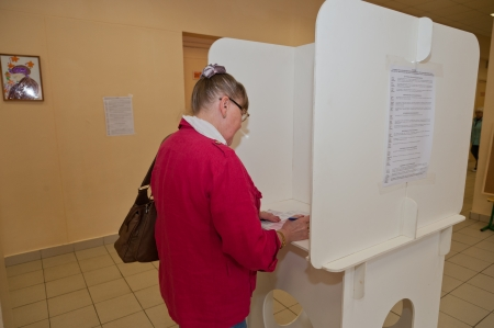 election commission: MOSCOW, RUSSIA - SEPTEMBER 8, 2013  Woman fills election ballot with the candidates for mayor of Moscow on September 8, 2013 at the local election commission in Moscow
