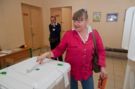 MOSCOW, RUSSIA - SEPTEMBER 8, 2013  Woman put election ballot with candidates for mayor of Moscow into the box on September 8, 2013 at the local election commission in Moscow