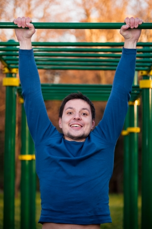 rekstok: Closeup of young strong athlete doing pull-up on horizontal bar Stockfoto