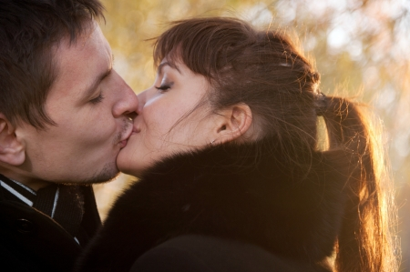 Closeup portrait of young kissing couple at sunshine with yellow leaves as background photo