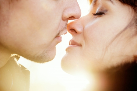 Closeup portrait of young kissing couple at sunshine Standard-Bild
